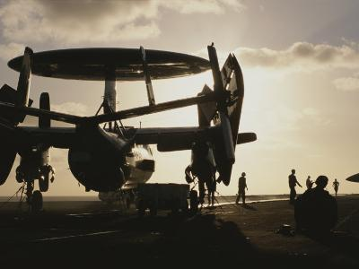 Military Personnel Stand Next to an Awacs Surveillance Plane