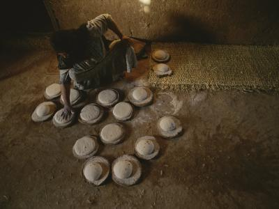 An Egyptian Woman Makes Loaves of Bread in a Traditional Manner