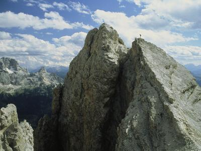 A Climber Standing at the Top of a Mountain in the Dolomites, Italy