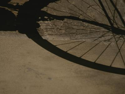 A Bicycle Wheel Casts a Shadow on a Wall and Sidewalk in Siena