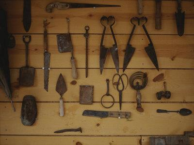 An Assortment of Hand Tools Hang on a Plank Wall