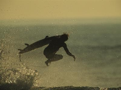 A Surfer and His Board Leap over Breaking Surf