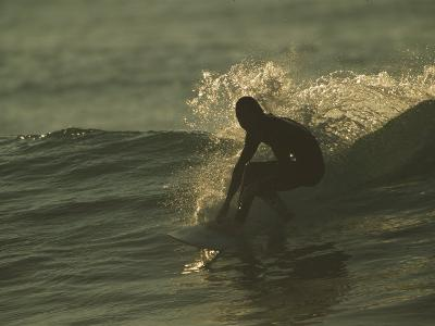 A Surfer Rides a Gentle Swell