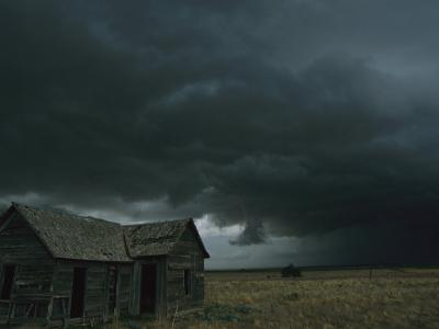 Heavy Dark Clouds Foretell a Possible Tornado Near an Old Homestead
