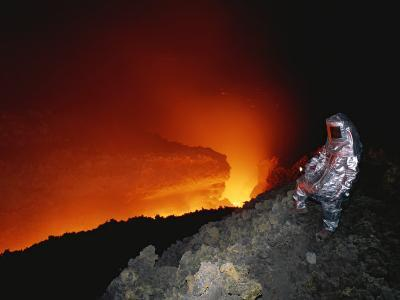 Scientist in Full Helmet and Thermal Suit Collects Lava Samples