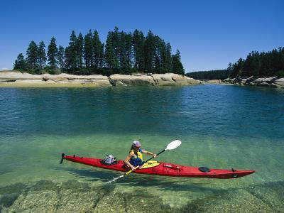 Woman Kayaks Through the Clear Water of Penobscot Bay, Maine