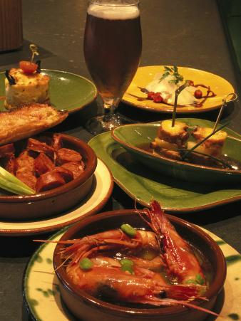 Several Dishes of Tapas and a Beer in a Spanish Restaurant