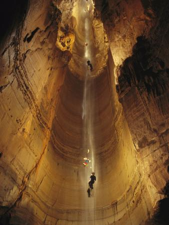 Cavers Cling to a Rope While Exploring the Cave