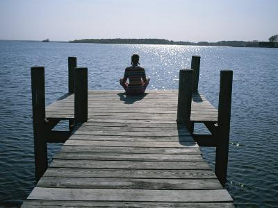 A Woman in a Yoga Pose at the End of a Dock