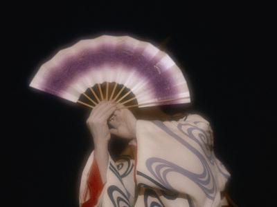 An Geisha Holds a Fan in Front of Her Face During a Formal Ceremony
