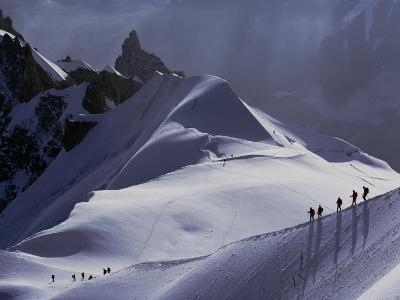 Hikers Follow a Path Across a Snow Field in the French Alps