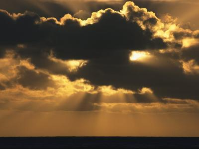 Rays of Sunlight Beam from Behind a Dark Cloud over Water at Twilight