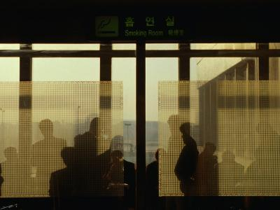 People Silhouetted in Smoking Room at Gimpo Airport, Seoul, South Korea