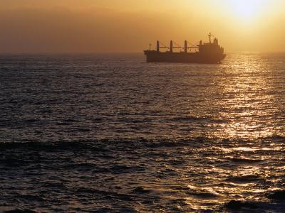Cargo Ship at Sea Silhouetted at Sunset, Chile
