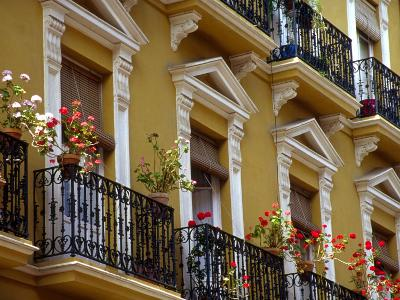 Spain, Sevilla, Andalucia Geraniums hang over iron balconies of traditional houses