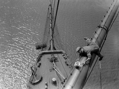 A Painter Lays Across the Rigging While Painting on Sailing Ship