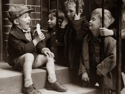 A Little Boy Holding a Banana Whilst Other Children Gaze Longingly at It