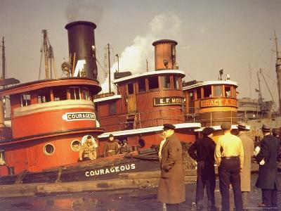 "Men at pier looking at 3 Tugboats, One Named ""Courageous"" with Crewmen on Deck"