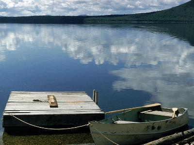 Rowboat Moored at Edge of Lake Showing Reflections of Clouds in Its Still Waters, in New England