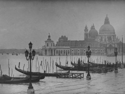 Moored Gondolas in Grand Canal by Flooded Piazza San Marco with Santa Maria Della Salute Church