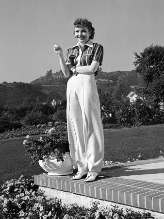 Actress Claudette Colbert Holding Cigarette as She Suns Herself on Terrace of Her Holmby Hills Home