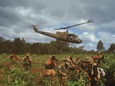 American UH1 Huey Helicopter Lifting Off as Personnel on the Ground Protect Themselves
