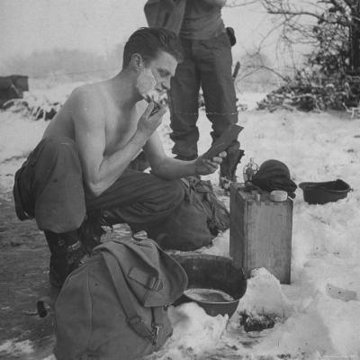 GI shaving with mirror during ull in the Ardennes Forest Conflict called the Battle of the Bulge