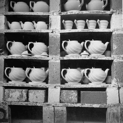 Cheap Chinaware Saucers, Cups, Teapots, Etc Standing on Racks in Pottery of the Hall China Co