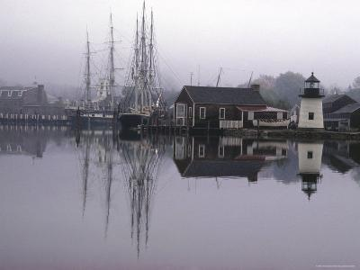 Scenic Harbor View with Masted Ships and Buildings Reflected in Placid Waters at Mystic Seaport