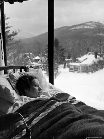 Female Tuberculosis Patient Lying under an Electric Blanket in Bed on Large Porch