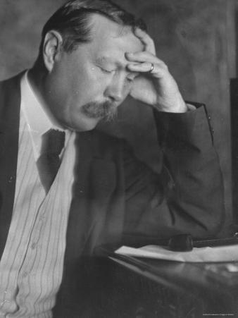 Photo by E. O. Hoppe of Author Sir Arthur Conan Doyle Seated, Eyes Downcast, in Reflective Pose