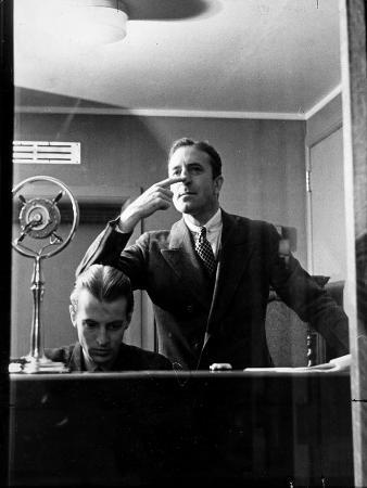 Wolfe, NBC Radio Director, Makes Timing Gestures Through the Glass Window of the Control Room
