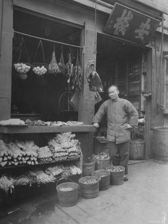 Vendor Standing Next to Vegetables, Eggs and Spices for Sale at Provision Market in Chinatown