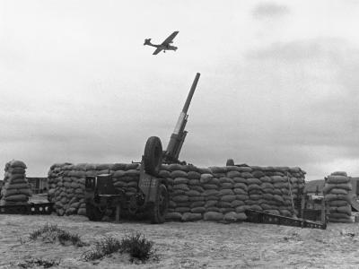 Plane Passing over Anti Aircraft Gun Position Protected by Sandbags, Part of Coastal Defenses