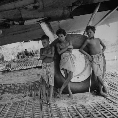 "Native Children Posing Next to Landing Gear of the American B-17 Bomber ""Frank Buck"" Bomber"