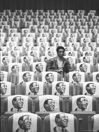 Comedian Bill Cosby Sitting in Empty Auditorium Filled with Copies of His Likeness on Each Seat