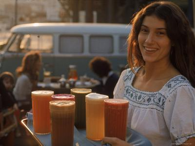 """Waitress Carrying Tray of Carrot, Celery. Beet, Orange, Apple, and Grapefruit Juice at """"The Source"""""""