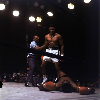 Heavyweight Boxer Cassius Clay, aka Muhammad Ali, Standing over Opponent Sonny Liston