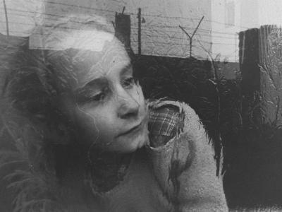 Girl Gazing Pensively Through Pane of Her Apartment Window, Grimly Reflects Image of Berlin Wall