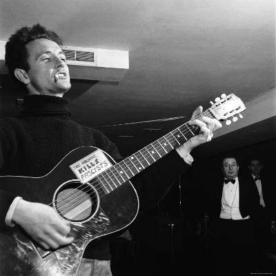 "Folk Singer Woody Guthie Performing with Guitar Emblazoned with ""This Machine Kills Fascists"""