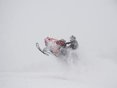 A Snowmobiler Jumps from a Hill on a Snowy Day