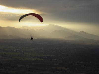 A Botanist Flies over a Field in a Powered Paraglider