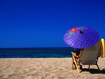 A Girl on the Beach Shading Under a Colourful Umbrella, Waikiki, Oahu, Hawaii, USA