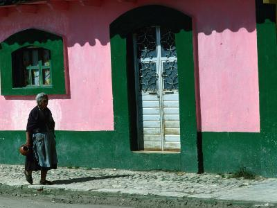Elderly Woman Walking Past Pink and Green Building, Chiapas, Mexico