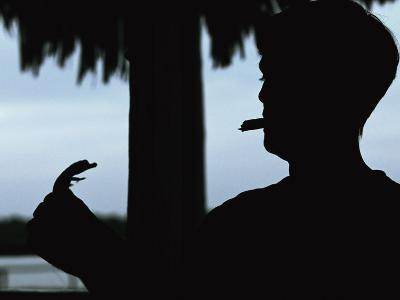 A Cigar-Smoking Cuban Man in Silhouette Holds a Baby Crocodile
