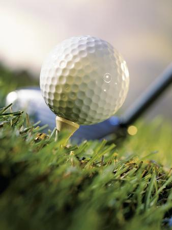 Golf Ball on Wooden Tee with Driver in Background