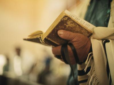 Man Holding a Prayer Book and Tefillin During a Synagogue Service, Israel