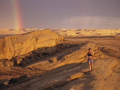 Woman Trail Running in a Rocky Landscape with a Rainbow