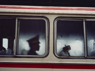 A Chinese Pla Soldier Sits on a Bus Behind a Tibetan Prayer Wheel