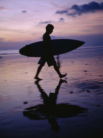 A Surfer Walks Along Kuta Beach at Dusk with His Surfboard in Hand